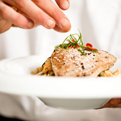 Chef adding final touch to tuna appetizer